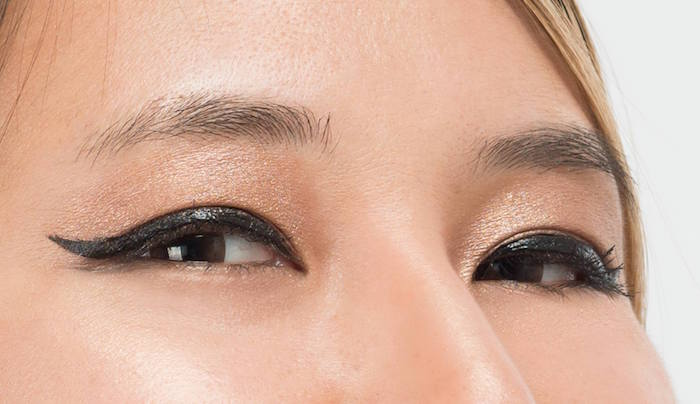 gold eyeshadow black eyeliner on woman with brown eyes blonde hair how to do a cat eye close up photo