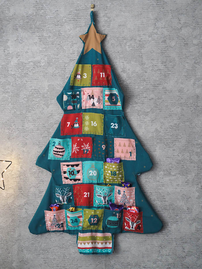 gray wall christmas countdown calendar made of fabric with small pockets in different colors filled with candy