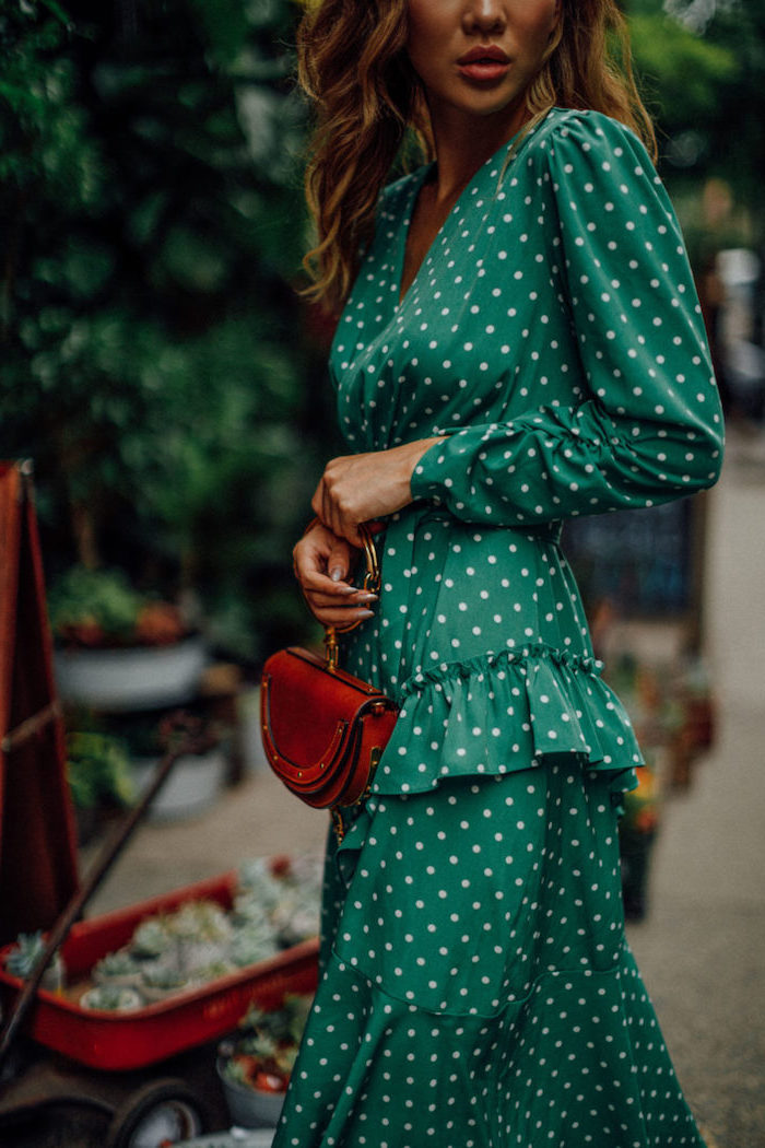 green dress with white dots and fringe long sleeves what to wear to a winter wedding worn by woman holding brown leather bag
