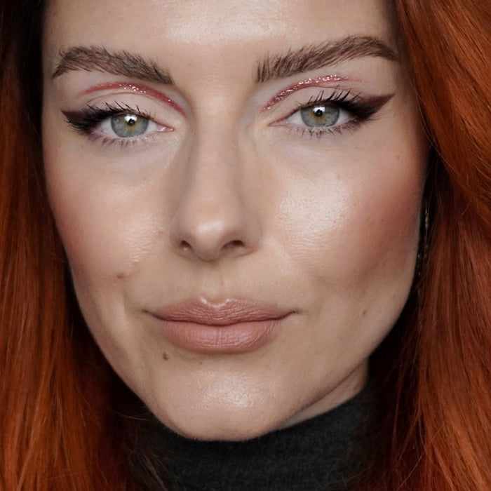 green eyed woman with thick eyebrows long red wavy hair how to do a cat eye with pink glitter