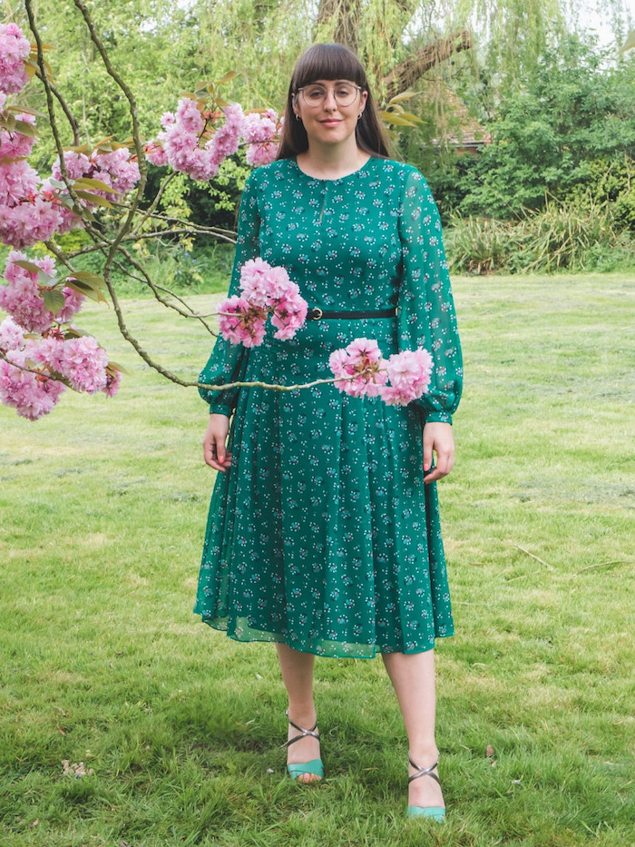 green floral dress with long puff sleeves worn by woman with brunette hair and bangs semi formal dresses for wedding with green sandals