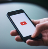 hand holding phone opening youtube on the phone youtube channels icon on white background