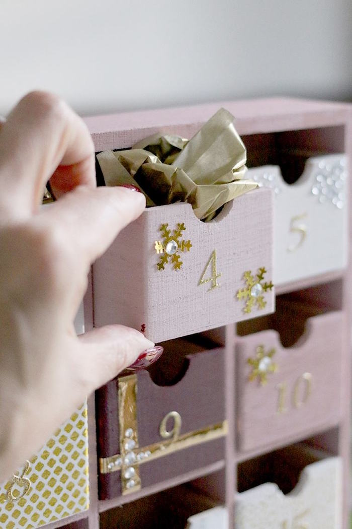 hand pulling out small box labeled with four painted in pink diy advent calendar ideas filled with candy and gold paper