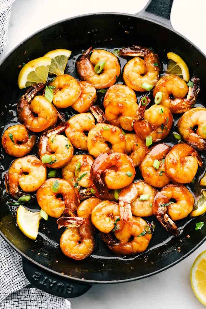 honey garlic butter shrimp cooked in black skillet garnished with chopped wild onion lemon slices placed on white surface