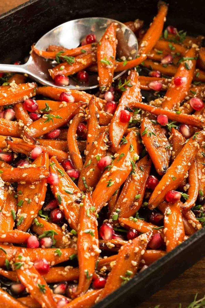 honey roasted carrots with pomegranate seeds inside black baking dish easy thanksgiving side dishes metal spoon