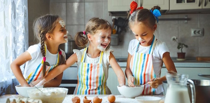 indoor activities for kids three girls wearing colorful aprons beating egss in white bowls flour on their faces