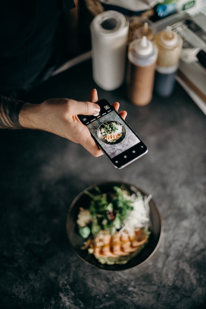 instagram followers hand holding phone taking picture of black plate filled with food placed on black surface