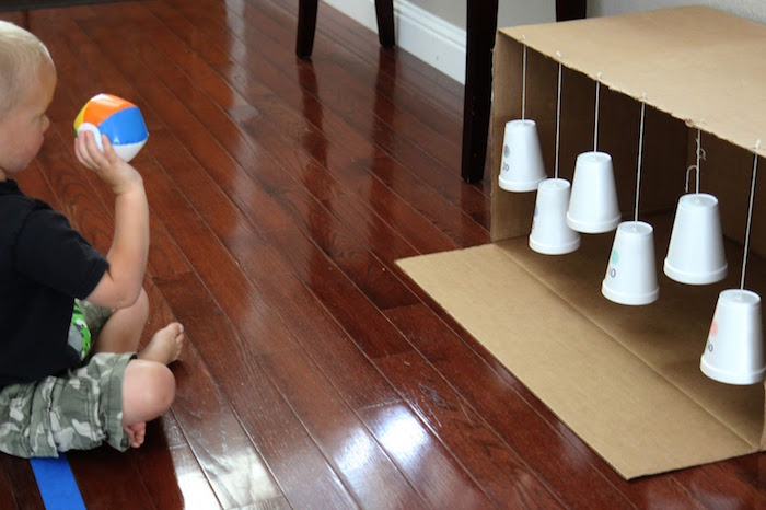 kid sitting on the floor throwing small ball at styrofoam cups hanging from carton box art and craft ideas for kids