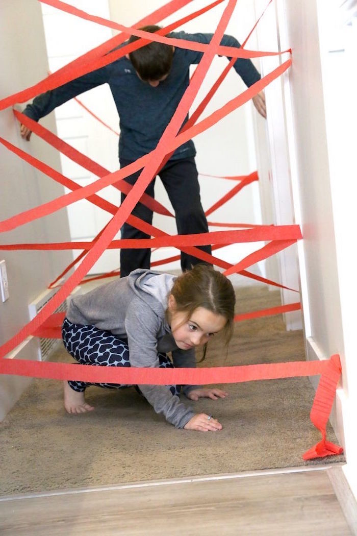 little boy and girl going through a hallway with red crepe paper attached to the walls activities for kids at home