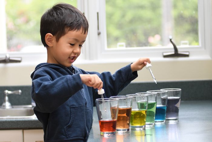little boy wearing black hoodie standing next to kitchen counter indoor activities for kids six glasses filled with water in different colors