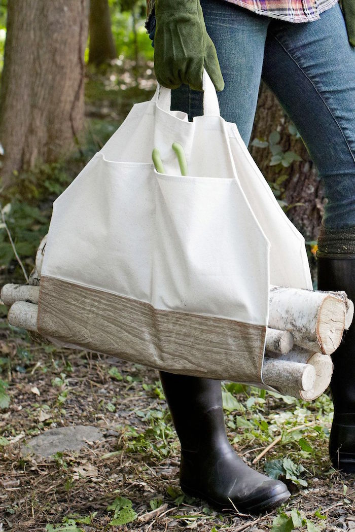 log carrier made from white fabric carried by woman wearing jeans black rubber boots and green mits good gifts for dad