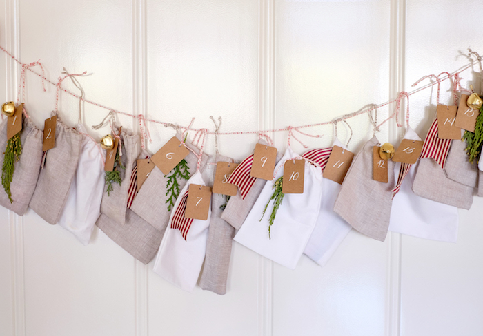 lots of bags in gray and white hanging on a string on white wall diy advent calendar decorated with ribbons and mistletoe