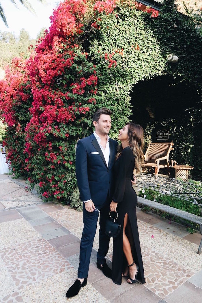 man and woman standing on sidewalk elegant dresses for wedding guests blue suit and long black dress with slits