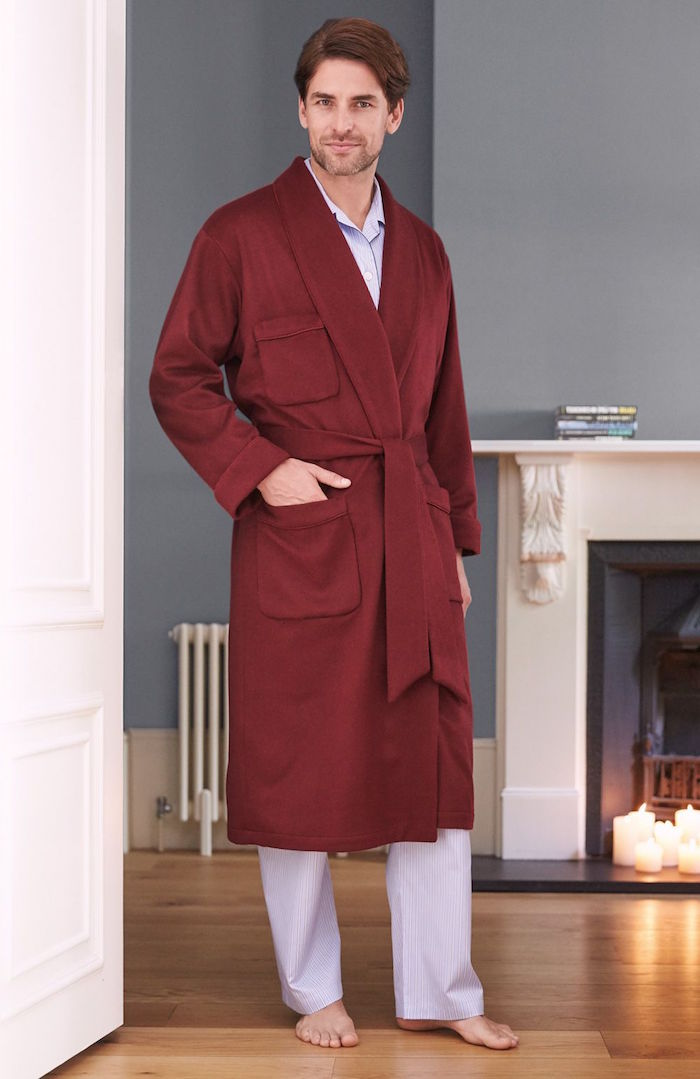man standing next to fireplace on wooden floor gifts for dad from daughter wearing white pyjamas and red robe