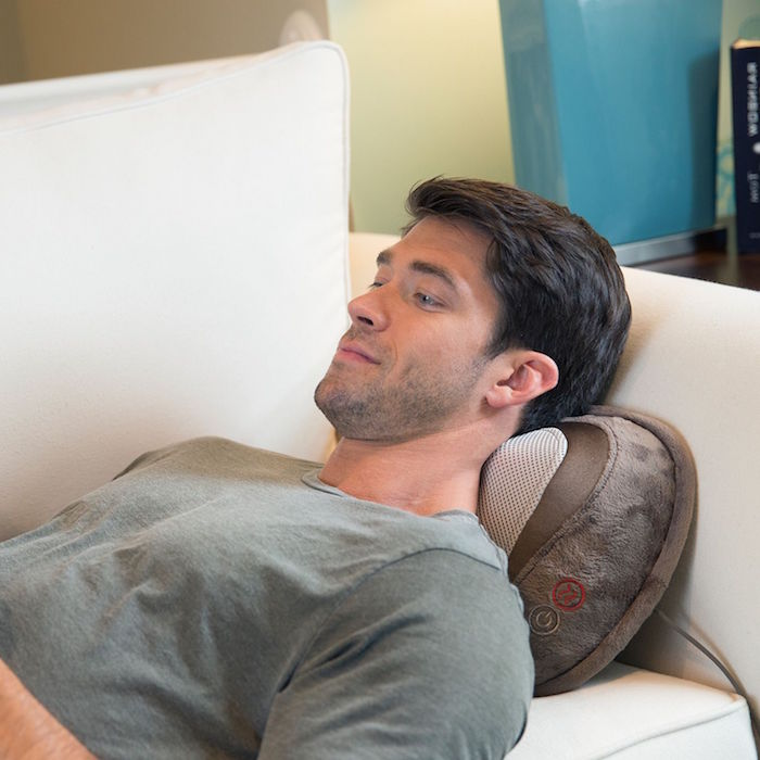 man wearing gray shirt laying on white sofa unique gifts for dad shiatsu massager pillow under his neck