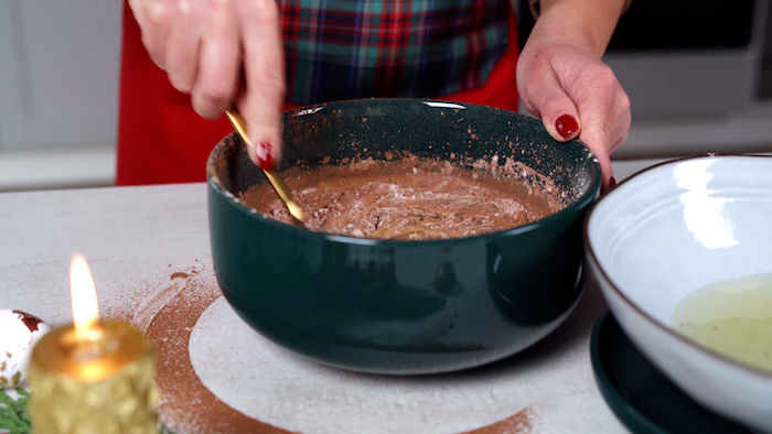 mixture for the cake batter being stirred with a spoon in green ceramic bowl christmas dinner party ideas