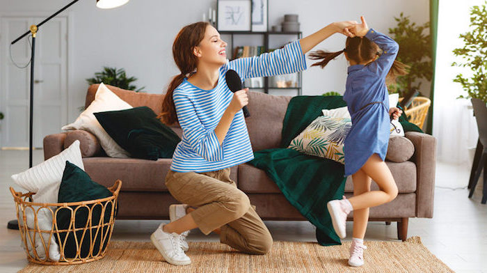 mom and daughter singing and dancing in front of brown sofa activities for kids at home white and green throw pillows and blanket