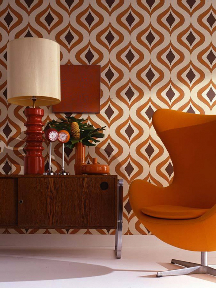 orange armchair placed next to wooden cabinet with lamp and clocks on it vintage wallpaper in orange gray and white