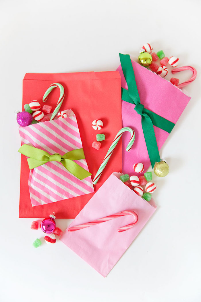 paper bags in pink and red filled with candy unique advent calendars tied with green ribbons placed on white surface