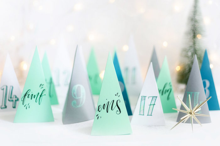 paper in the shape of christmas tree in different colors white gray blue mint green placed on white surface advent calendar