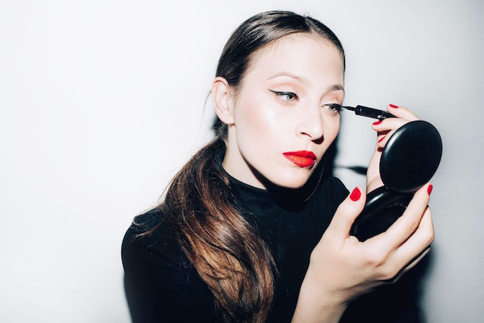 photo of woman putting eyeliner on her eyes holding a mirror how to do a cat eye wearing black blouse