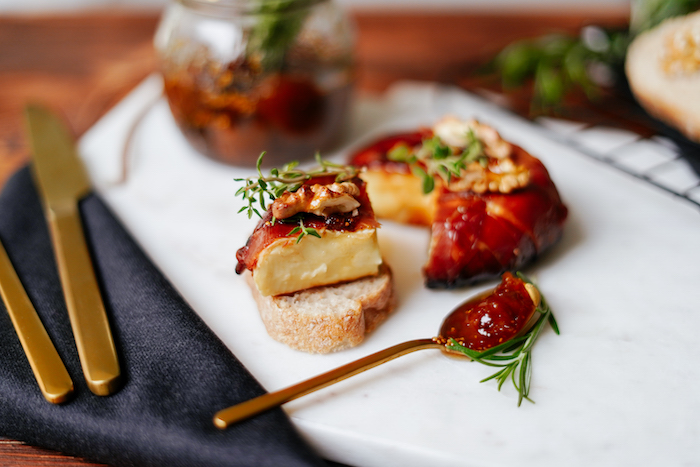 piece of baked brie wrapped in prosciutto on slice of bread thanksgiving food ideas covered with jam thyme walnuts