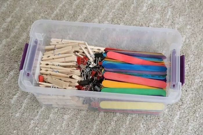 plastic container filled with clothespins fun things to do with kids popsicle sticks painted in different colors