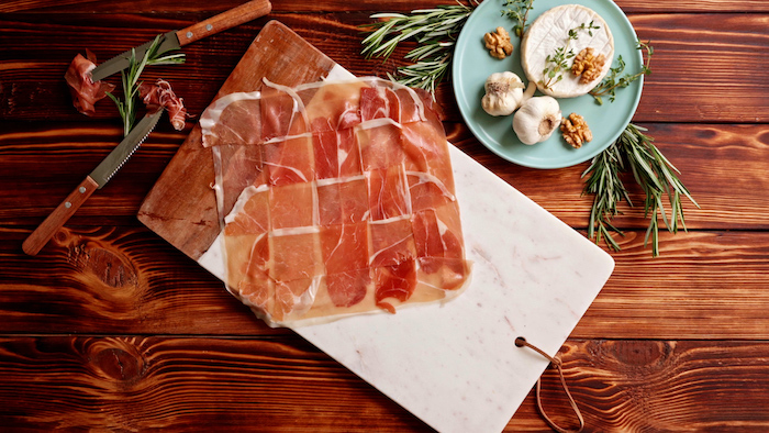 prosciutto slices arranged together thanksgiving dinner ideas spread on marble cutting board placed on top of wooden surface