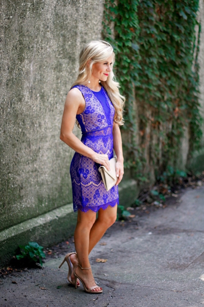 purple lace dress worn by blonde woman womens wedding guest dresses with nude sandals and clutch bag