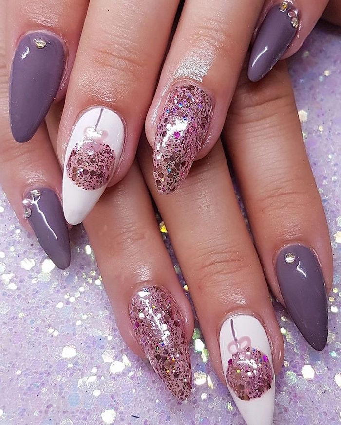 purple white and rose gold glitter nail polish on long stiletto nails holiday nail designs bauble decorations on middle fingers