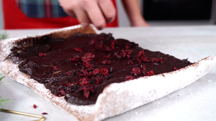 putting hazelnut spread and dried cranberries on batter christmas party food ideas buffet covered with powdered sugar