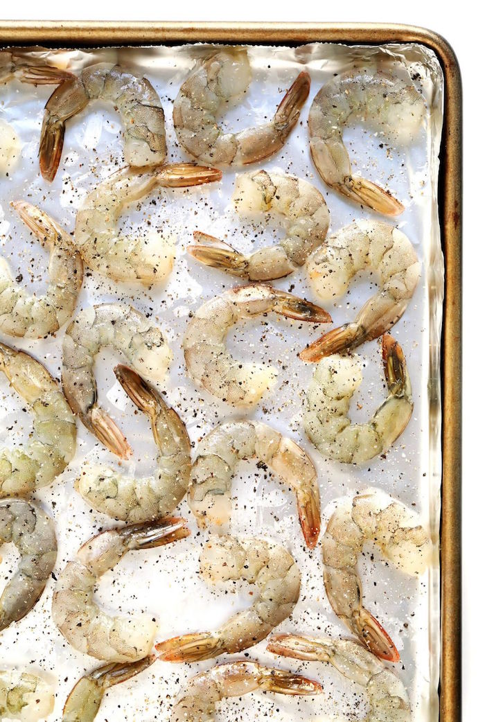 raw shrimp garnished with herbs arranged on paper lined baking sheet shrimp dinner ideas