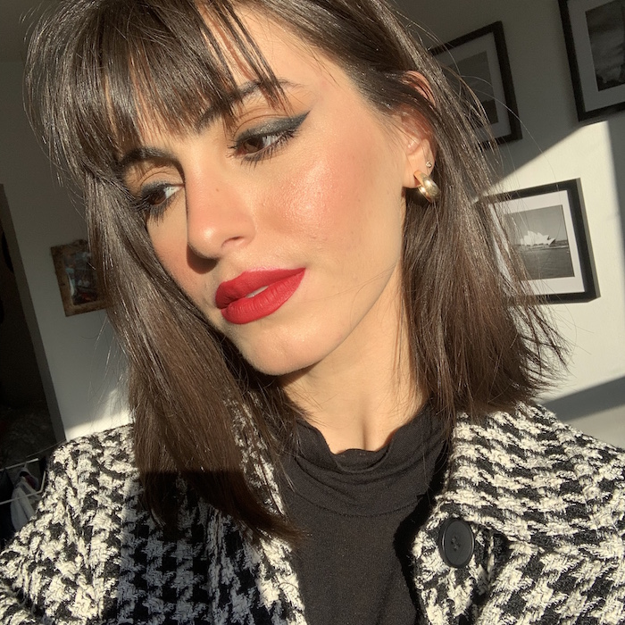 red lipstick on woman with shoulder length brunette hair with bangs how to do a cat eye wearing black polo blouse black and white coat