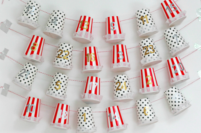 red white and black paper cups labeled with numbers hanging from red and white strings hanging on white wall homemade advent calendar