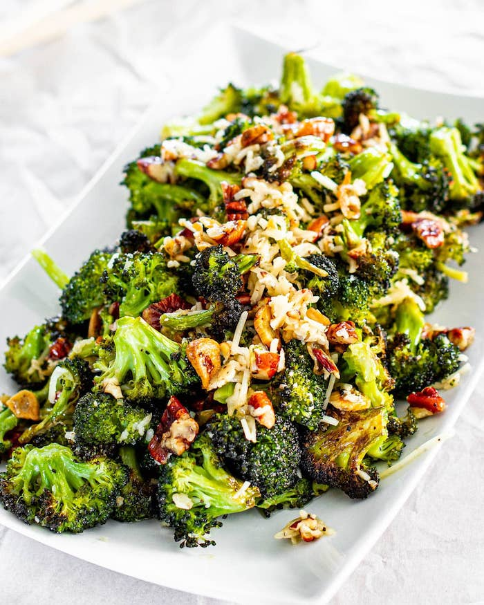 roasted broccoli with cheese walnuts placed on white plate what to make on thanksgiving placed on white surface