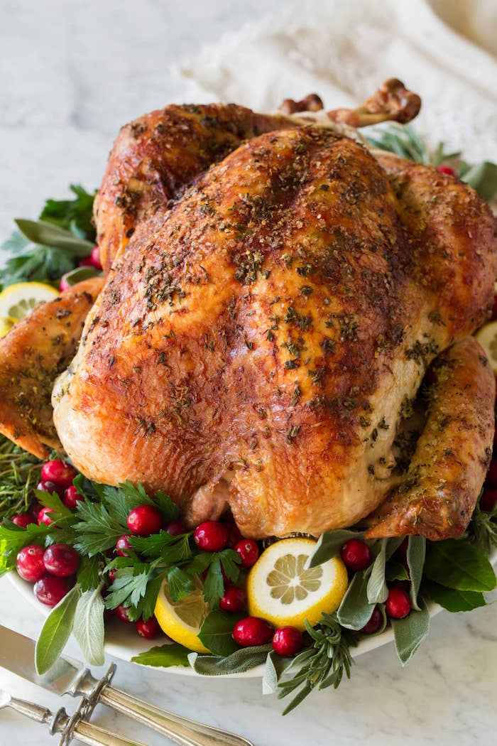 roasted christmas turkey placed on white tray easy christmas dinner ideas decorated with green herbs cranberries lemon slices