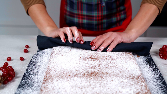 rolling up the cake batter with the towel christmas party food ideas buffet covered with powdered sugar