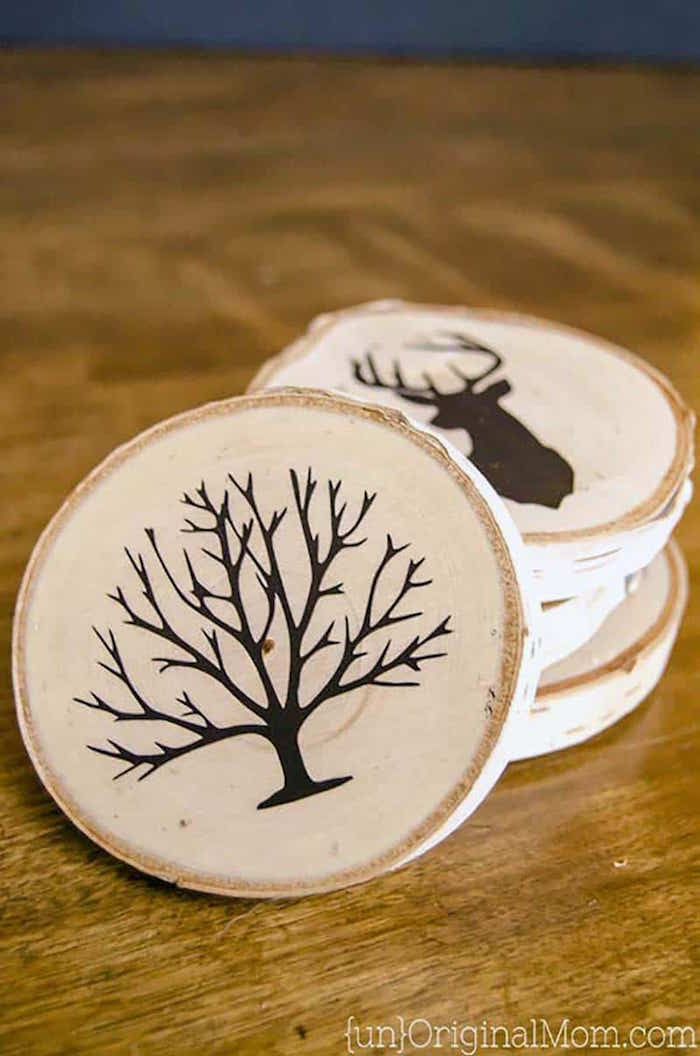 set of wood coasters with different drawings on them what to get dad for christmas arranged on wooden surface