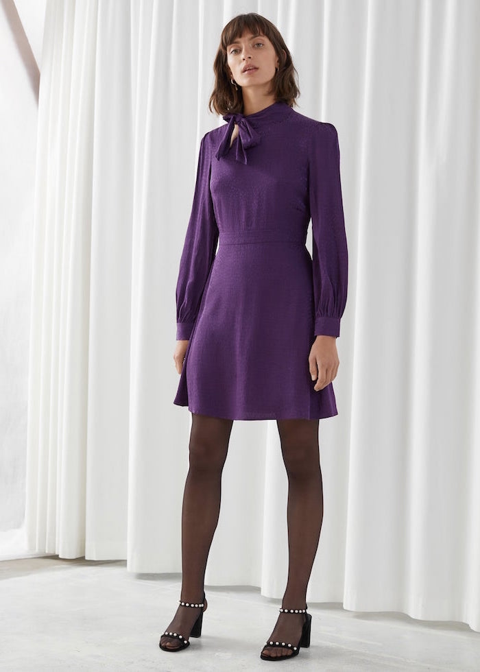 short purple dress with bow and long sleeves worn with black tights sandals womens wedding guest dresses worn by brunette woman