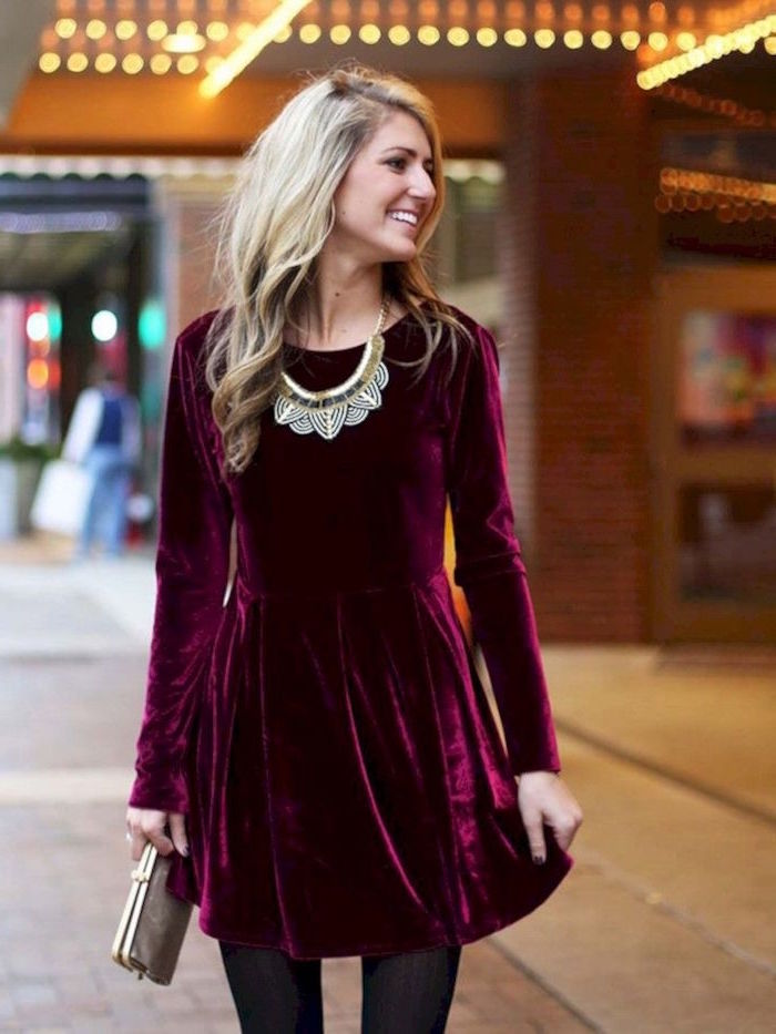 short red velvet dress worn with black tights by blonde woman formal wedding guest dresses standinf on sidewalk