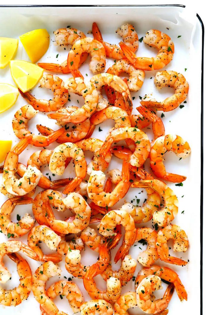 shrimp dinner ideas shrimp with herbs arranged on paper lined white baking sheet lemon wedges on the side