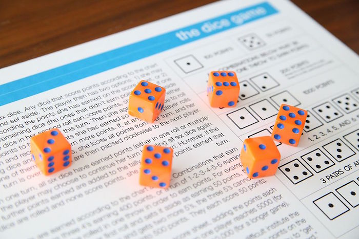 six orange dice with blue dots fun things to do with kids paper with the rules of the dice game written on it