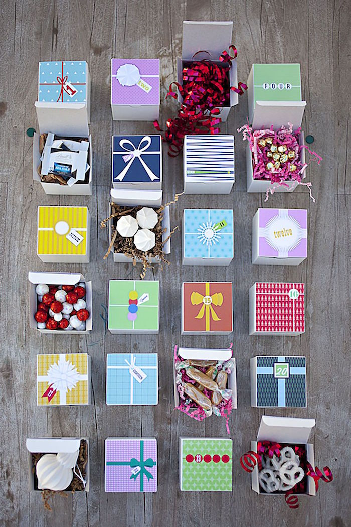 small boxes decorated with different paper diy advent calendar different candy inside each placed on wooden surface