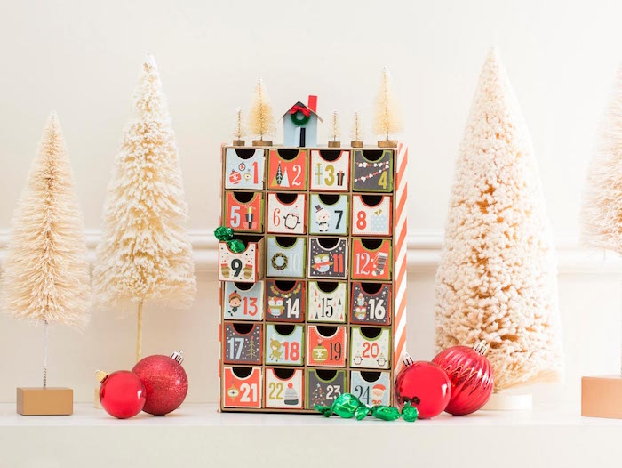 small wood christmas countdown calendar with little boxes with numbers decorated in different colors small white faux trees around them red baubles