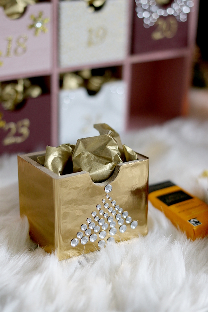 small wooden box painted in gold decorated with rhinestones filled with candy and gold paper christmas tree advent calendar