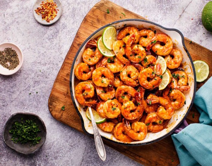 spicy honey lime shrimp baked in white skillet how long to cook shrimp placed on wooden cutting board bowls with herbs on the side