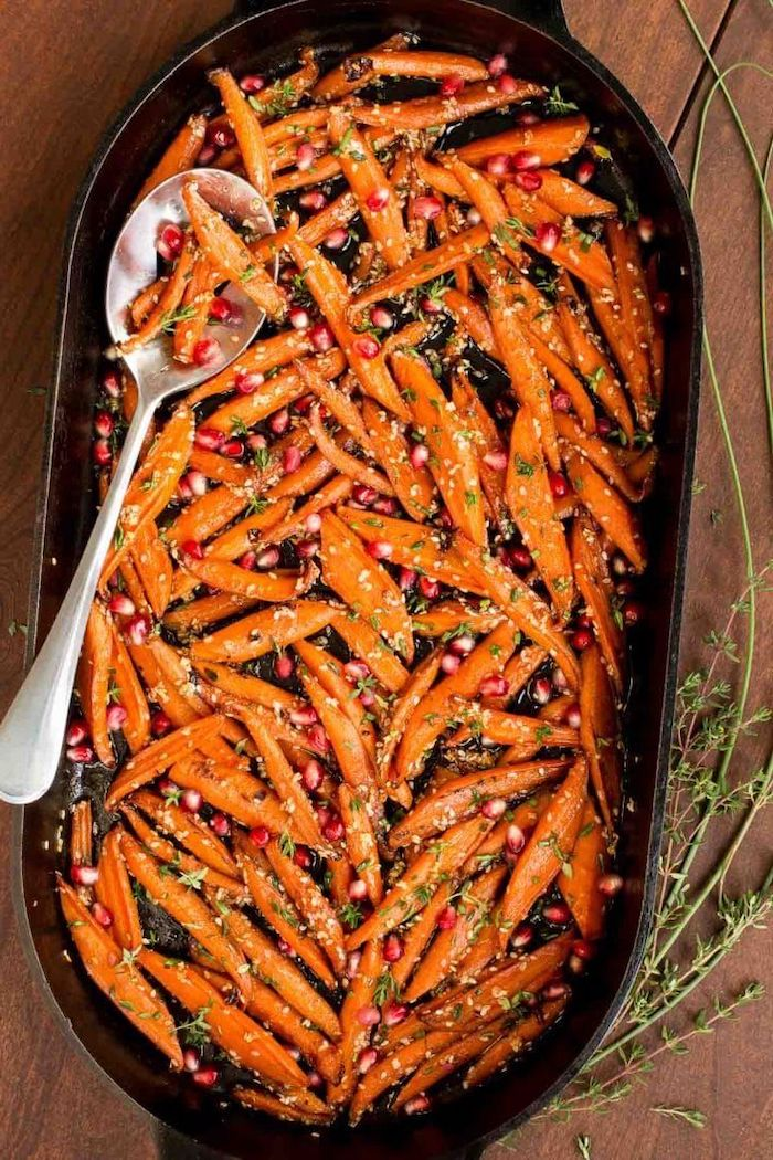 spoon inside black baking dish easy thanksgiving side dishes honey roasted carrots with pomegranate seeds