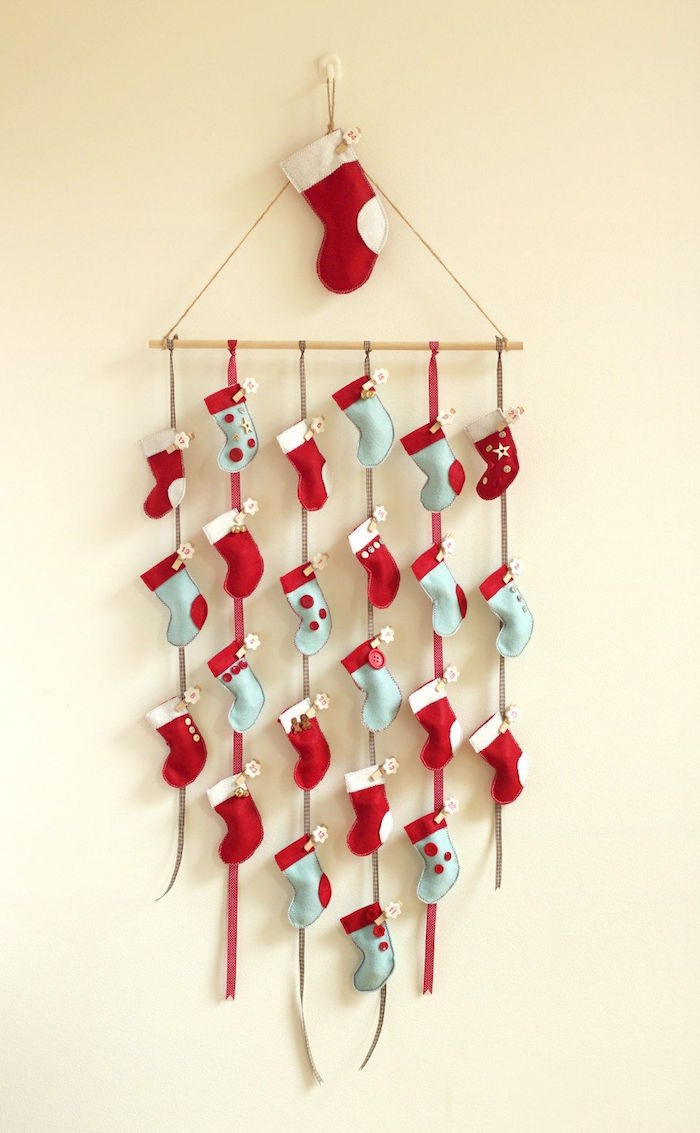 stockings hanging on ribbons on white wall diy advent calendar different colors red and white gray and red