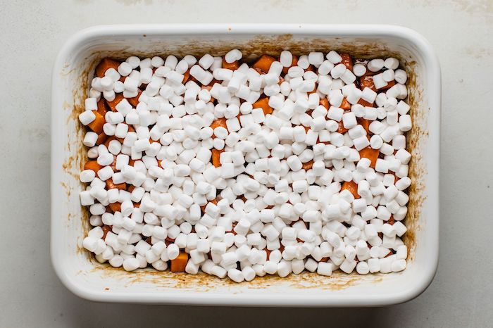 sweet potatoes cut into cubes placed in white casserole dish best thanksgiving sides covered with marshmallows