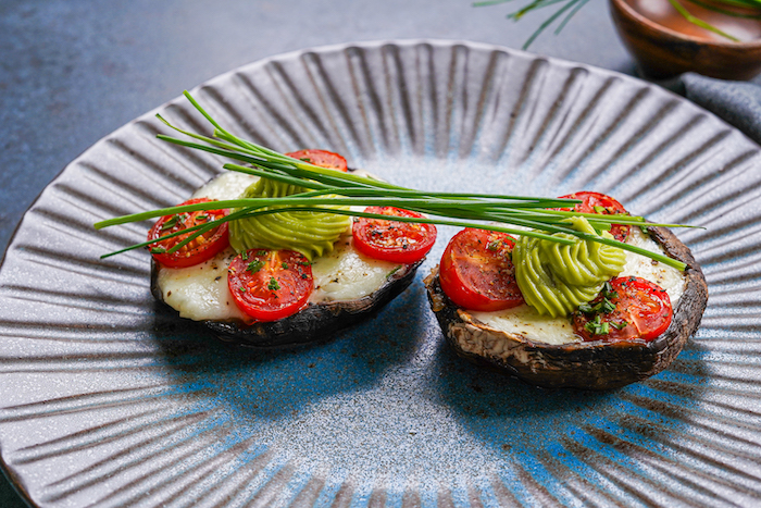 thanksgiving side dish recipes stuffed portobello mushrooms with baby mozzarella cherry tomatoes placed on black plate